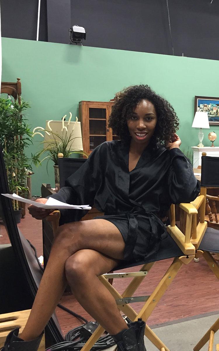 Actress Carrie Bernans sitting in a director's chair holding a script
