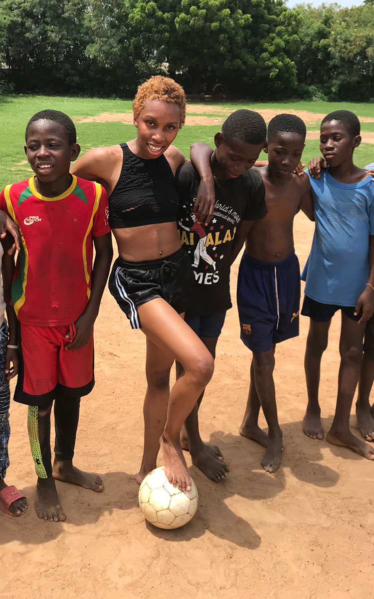 Actress Carrie Bernans playing football with kids