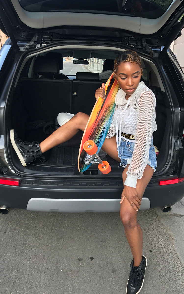 Actress Carrie Bernans holding a longboard in the back of a car